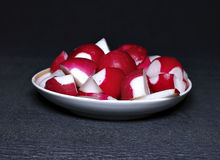 Sliced red fresh radishes on a plate. On a dark background Stock Images