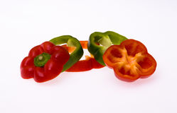 Sliced red and green bell peppers. Arrangement of sliced red and green bell peppers isolated on white Royalty Free Stock Photography