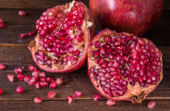 Sliced red pomegranate on rustic wooden desk. Royalty Free Stock Photos