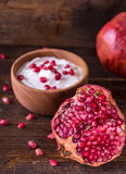 Sliced red pomegranate on wooden desk with yogurt in behind. Stock Photo
