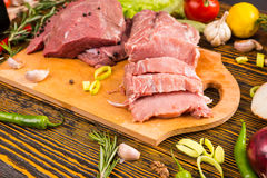 Sliced red raw meat on cutting board. Over wood grain table with various fresh vegetables and herbs surrounding it Stock Images