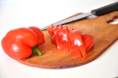 Sliced red sweet pepper on a cutting board. Red sweet bell pepper sliced strips  on white background cutout Stock Photo