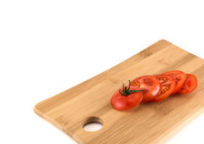 Sliced red tomatoes composition background. Sliced red tomatoes composition over wooden cutting board as copyspace background Royalty Free Stock Images