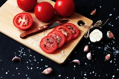 Sliced red tomatoes with salt and garlic on a dark background royalty free stock photos