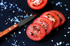 Sliced red tomatoes with salt and garlic on a dark background royalty free stock images