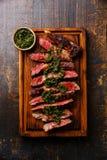 Sliced Ribeye steak with chimichurri sauce. Sliced medium rare grilled beef barbecue Ribeye steak with chimichurri sauce on cutting board on dark background Stock Photo