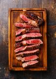 Sliced Ribeye steak. Sliced medium rare grilled beef barbecue Ribeye steak on cutting board on dark background Royalty Free Stock Photography
