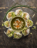 Sliced rice rolls lined circle around a bowl of vegetable soup on wooden background top view Stock Photo