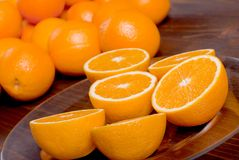 Sliced ripe appetizing delicious orange on brown table Stock Images