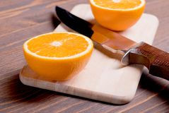 Sliced ripe appetizing delicious orange on cutting board next to Royalty Free Stock Photo