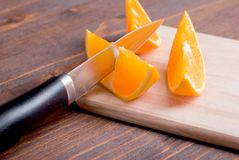Sliced ripe appetizing delicious orange on cutting board next to Royalty Free Stock Images