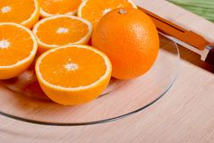 Sliced ripe appetizing orange on a cutting board on a green tabl. Sliced ripe appetizing orange on cutting board on a green table Royalty Free Stock Image