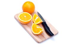 Sliced ripe appetizing orange on a cutting board next to a knife Royalty Free Stock Photos