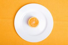 Sliced ripe appetizing orange on a white plate on a yellow napki Stock Photo