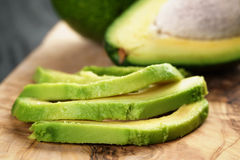 Sliced ripe avocados on olive cutting board Stock Photography
