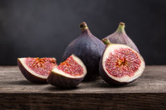 Sliced ripe figs. On a wooden table. Black background Royalty Free Stock Image