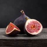 Sliced ripe figs. On a wooden table. Black background royalty free stock photo