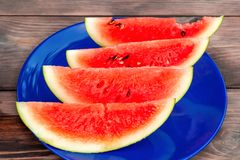 Sliced ripe red watermelon on a blue plate on a wooden table stock photo