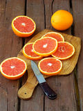 Sliced ripe Sicilian blood orange on an wooden cutting board. Royalty Free Stock Photos