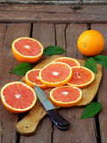 Sliced ripe Sicilian blood orange on an wooden cutting board. Stock Images