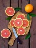 Sliced ripe Sicilian blood orange on an wooden cutting board. Stock Photos