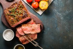 Sliced Roast beef on cutting board with grilled vegetables. Top Royalty Free Stock Photo