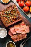 Sliced Roast beef on cutting board with grilled vegetables. Top Stock Image