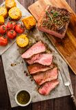 Sliced Roast beef on cutting board with grilled vegetables. Top Stock Photography