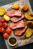 Sliced Roast beef on cutting board with grilled vegetables. View Royalty Free Stock Image