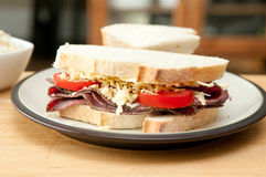 Sliced roast beef sandwich. With cheese and tomato and cole slaw Royalty Free Stock Photography