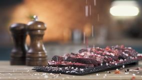 Sliced roast meat on a black stand. cook sprinkle pepper and salt with his hands . Close-up, Slow motion. Sliced roast meat on a black stand. cook sprinkle stock video footage
