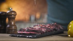 Sliced roast meat on a black stand. the cook sprinkles red pepper and salt with his hands . Close-up, Slow motion. Sliced roast meat on a black stand. the cook stock footage
