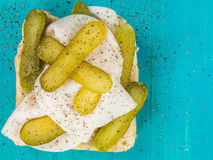 Sliced Roast Turkey With Gherkin Pickles Open Sandwich With Ground Black Pepper Seasoning. Sliced Roast Turkey With Gherkin Pickles Open Sandwich Against a Blue stock photo