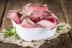 Sliced Roastbeef on wooden background. Portion of sliced Roastbeef on an old vintage wooden table (selective focus Stock Photography