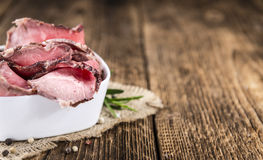 Sliced Roastbeef on wooden background. Portion of sliced Roastbeef on an old vintage wooden table (selective focus Royalty Free Stock Images
