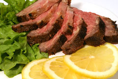Sliced roasted meat with lemon. Sliced grilled meat on lettuce, wirh lemon Stock Images