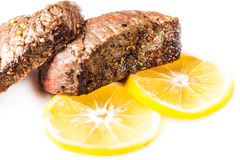 Sliced roasted meat with slices of lemon closeup Royalty Free Stock Photography