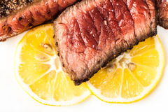 Sliced roasted meat with slices of lemon Royalty Free Stock Photo