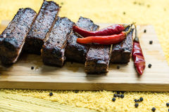 Sliced roasted pork ribs with red pepper on the board Stock Photos