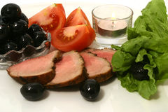 Sliced roasted red meat. Red meat on white dish with olives and vegetables Stock Images