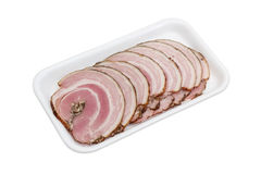 Sliced roll of a baked pork belly on plastic tray Stock Photo