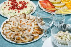 Sliced rolls from chicken or turkey meat stuffed with vegetables on banquet table. Vegetable and fruit salad, sliced apple, orange. And empty wine glasses. Side royalty free stock photos