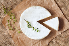 Sliced round camembert cheese traditional milk. Creamy dairy product with thyme on vintage parchment. Rustic style and natural light. Top view. Rustic sacking Stock Photo