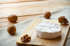 Sliced round camembert cheese on a wooden board with nuts Royalty Free Stock Photos