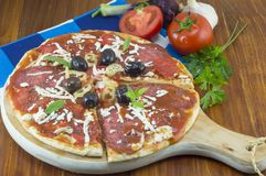 Sliced round pizza and raw vegetables on a wooden table Royalty Free Stock Photos