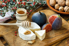 Sliced round of soft ripe creamy French Camembert cheese served with fresh juicy ripe red figs, honey and walnuts on a wooden back. Ground. Closeup Royalty Free Stock Photo
