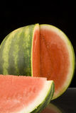 Sliced Round Watermelon. A round watermelon with a section cut from it and laying on it's side Stock Images