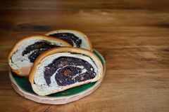 Sliced ruddy fresh bread with poppy seeds lying on a round clay plate on a wooden surface with copyspace stock image