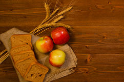 Sliced rye bread, apples and ears of corn on sackcloth, wooden table Stock Image