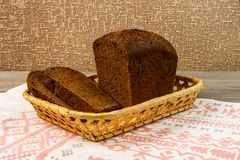 Sliced rye bread in a basket standing on a towel. A loaf of fresh rye bread with slices on a wooden rustic table. Royalty Free Stock Image